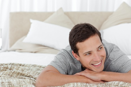 unbend: Cheerful man lying in his bedroom Stock Photo