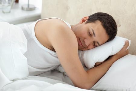 Cute man sleeping peacefully on his bed