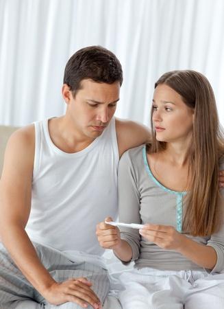 prueba de embarazo: Hombre mirando una prueba de embarazo con su novia Foto de archivo