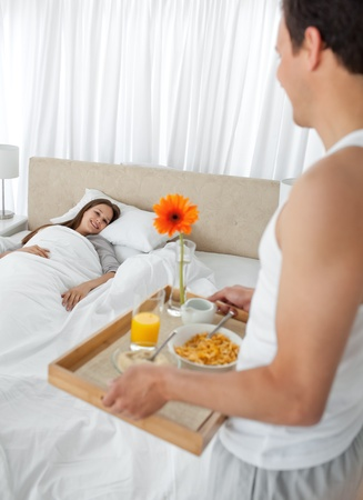 Passionate man bringing the breakfast to his girlfriend in the bedroom photo