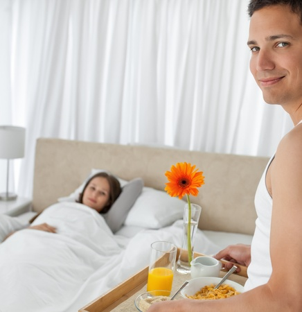 Portrait of a man bringing the breakfast to his girlfriend photo
