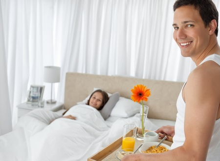 Happy man bringing the breakfast to his girlfriend on the bed photo