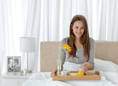 Portrait of a young woman having breakfast on the bed photo