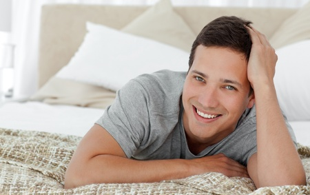 Joyful man lying on th edge of his bed at home photo