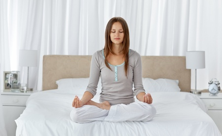 in pajama: Young woman doing yoga exercises on the bed Stock Photo