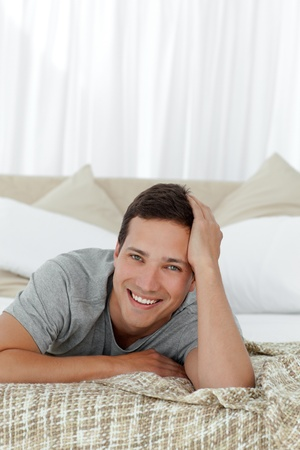Portrait of a cheerful man lying on his bed photo