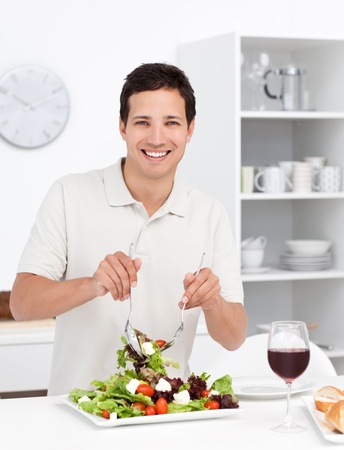 Happy man mixing a salad standing in the kitchen photo