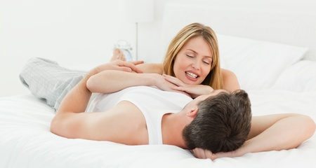 Lovely couple lying down together in their bed at home Stock Photo - 10212811