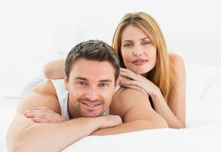Lovely couple lying down together in their bed at home Stock Photo - 10207156