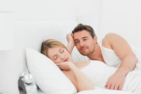 Boyfriend looking at his girlfriend who is  sleeping photo