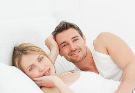 Cute couple lying down together in their bed