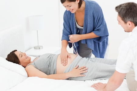 Pregnant woman with her husband and a nurse photo