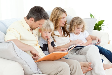 reading room: Family reading a book on their sofa Stock Photo