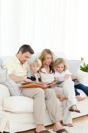 Family reading a book on their sofa Stock Photo - 10170440