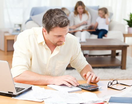 Man calculating his bills while his family are on the sofa Stock Photo - 10212896