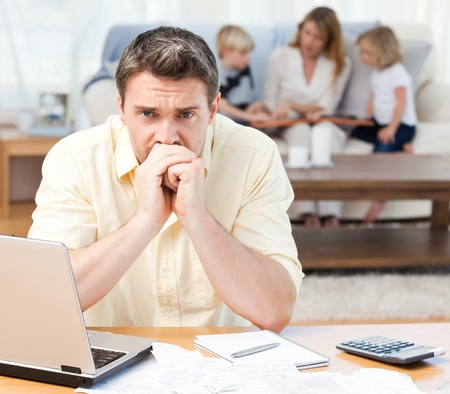 Man calculating his bills while his family are on the sofa photo