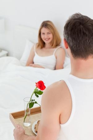 Joyful lovers having breakfast in their bed photo