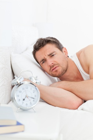An angry man in his bed before waking up photo