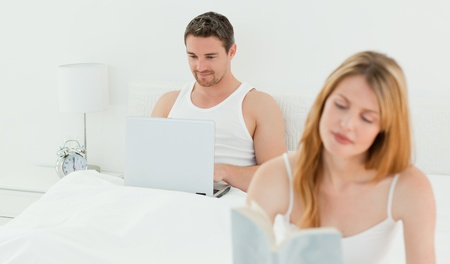 Man is on his laptop while his wife is reading a book photo