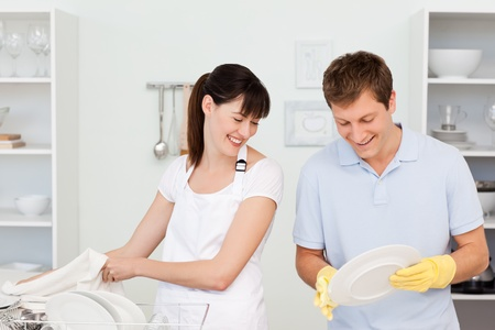 wash dishes: Lovers washing dishes together