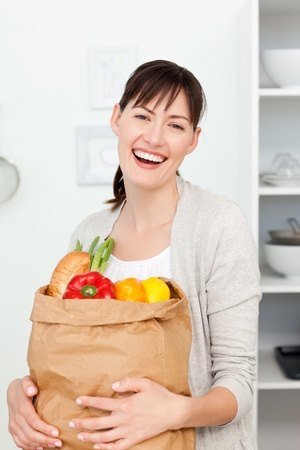 Woman with shopping bags in the kitchen  photo