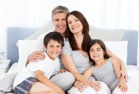 convivencia familiar: Familia acostado en su cama Foto de archivo