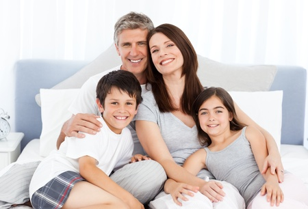 family life: Family  lying down on their bed Stock Photo