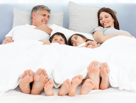 Family lying down in their bed photo