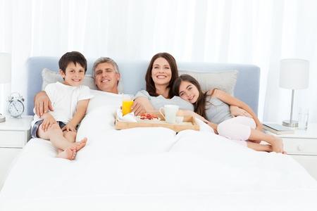 mujer en la cama: Familia desayunando en su cama
