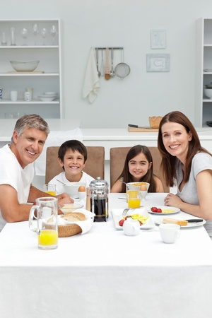 Family having breakfast in the kitchen photo