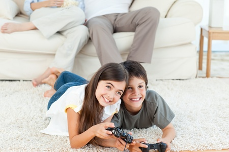 Children playing video games at living room photo