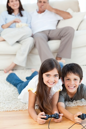 ni�os jugando videojuegos: Ni�os jugando juegos de video, mientras que los padres est�n hablando Foto de archivo