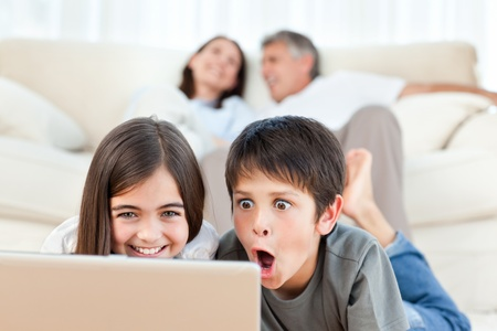 Lovely children watching a movie on their laptop at home photo
