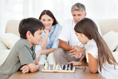 Parents looking their children playing chess Stock Photo - 10212630