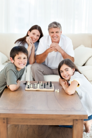 chess men: Portrait of a little family in their living room Stock Photo