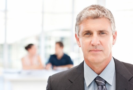 Businessman looking at the camera while his team is working  photo