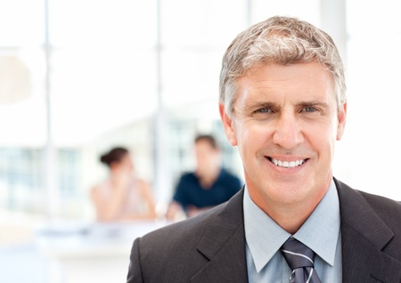 Businessman looking at the camera while their team is working  photo