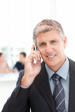 Businessman phoning while his team is working  photo