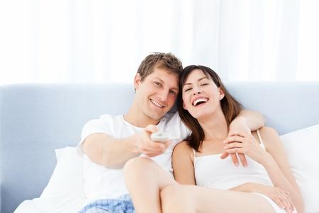 pareja viendo tv: Sonriente pareja viendo la televisi�n en su casa