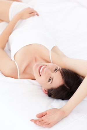 Pretty woman lying down on her bed photo