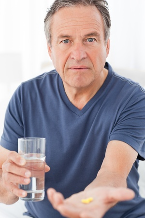 Mature man taking medicine Stock Photo - 10198601