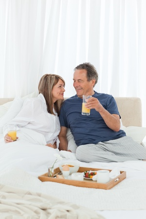 Lovely couple  having breakfast in their bed at home Stock Photo - 10215368