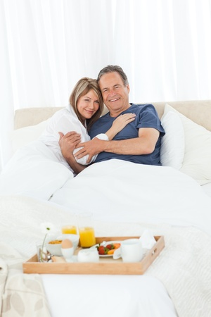 Lovely couple  having breakfast in their bed at home Stock Photo - 10214752