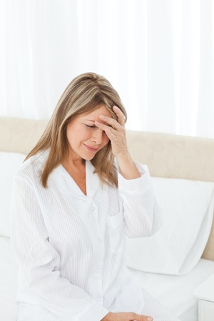 bother: Woman having a headache on her bed Stock Photo