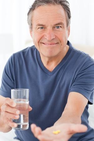 Sick man taking his pills at home Stock Photo - 10198823