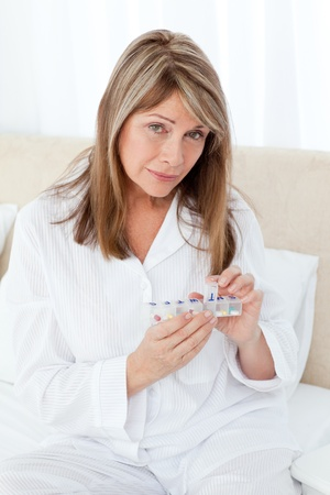 wincing: Sick woman taking her pills at home