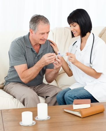 home health nurse: Nurse showing pills to her patient Stock Photo