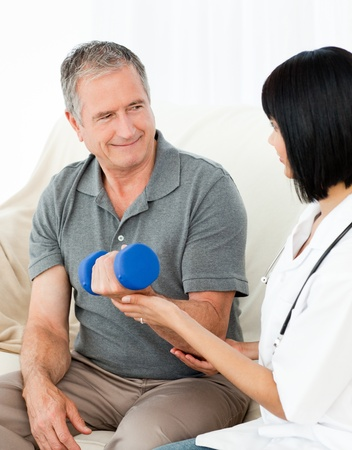 age test: Nurse helping her patient to do exercises at home