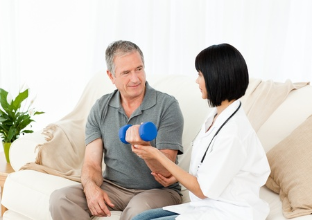 Nurse helping her patient to do exercises at home Stock Photo - 10218873