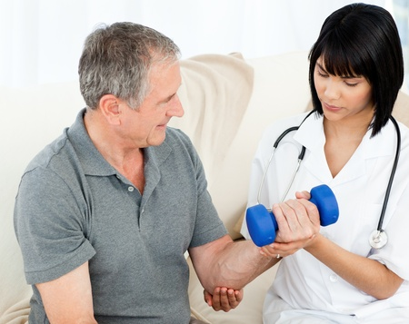 Nurse helping her patient to do exercises at home Stock Photo - 10219976